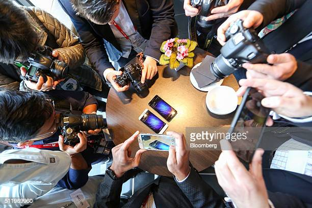 Attendees take photographs of the Mi5 smartphone manufactured by Xiaomi Corp during its launch at the Mobile World Congress in Barcelona Spain on...