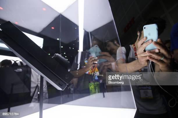 Attendees take photographs of the Microsoft Corp Xbox One X video game console on display during the E3 Electronic Entertainment Expo in Los Angeles...
