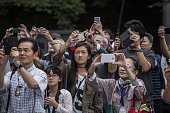 Attendees take photographs of the procession during the Soma Nomaoi festival at the Nakamura Shrine in Soma Fukushima Prefecture Japan on Saturday...