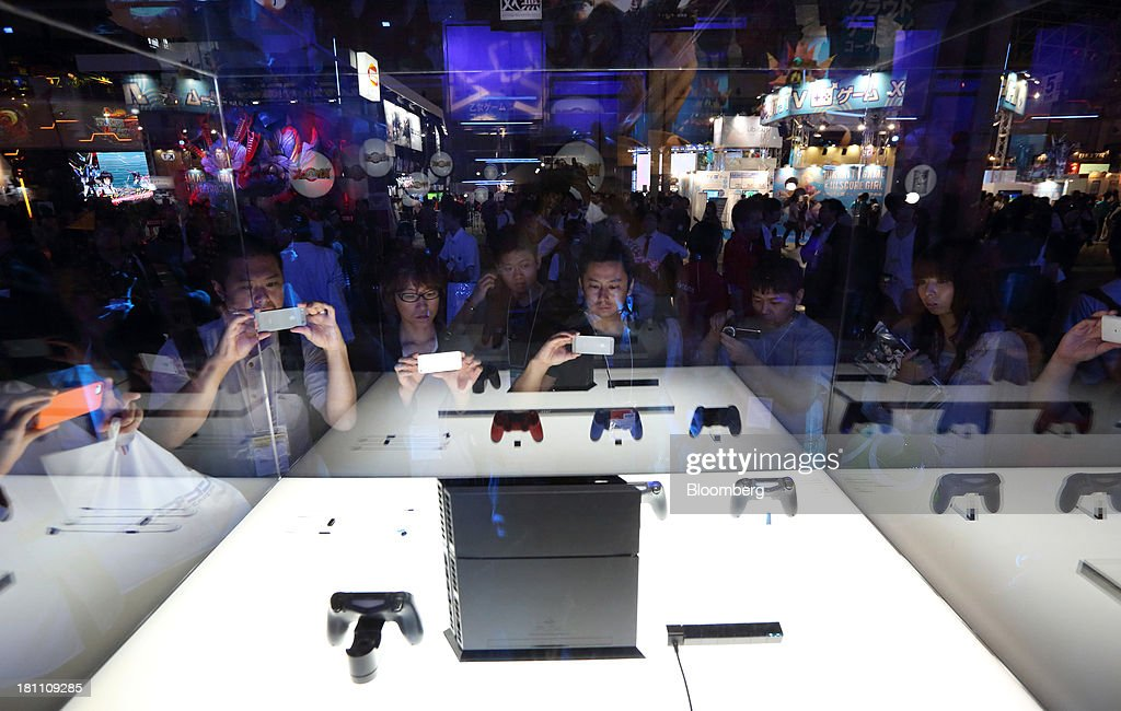 Attendees take photographs of the Sony Computer Entertainment Inc. PlayStation 4 (PS4) video game console and controllers at the Tokyo Game Show 2013 in Chiba, Japan, on Thursday, Sept. 19, 2013. Sony Corp. expects sales of its new PlayStation 4 console to reach 5 million units this financial year, with at least 20 games to be available as it competes with a new machine from Microsoft Corp. Photographer: Tomohiro Ohsumi/Bloomberg via Getty Images