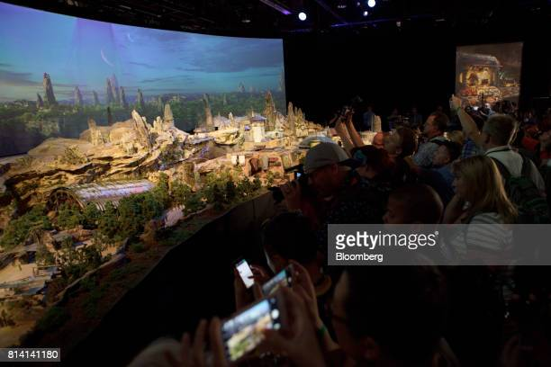 Attendees take photographs of the Walt Disney Co 'Star Wars' lands 3D model unveiled ahead of the D23 Expo in Anaheim California US on Thursday July...