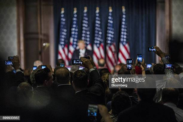 Attendees take photographs with their smartphones as Donald Trump 2016 Republican presidential nominee speaks during a campaign event at the Union...