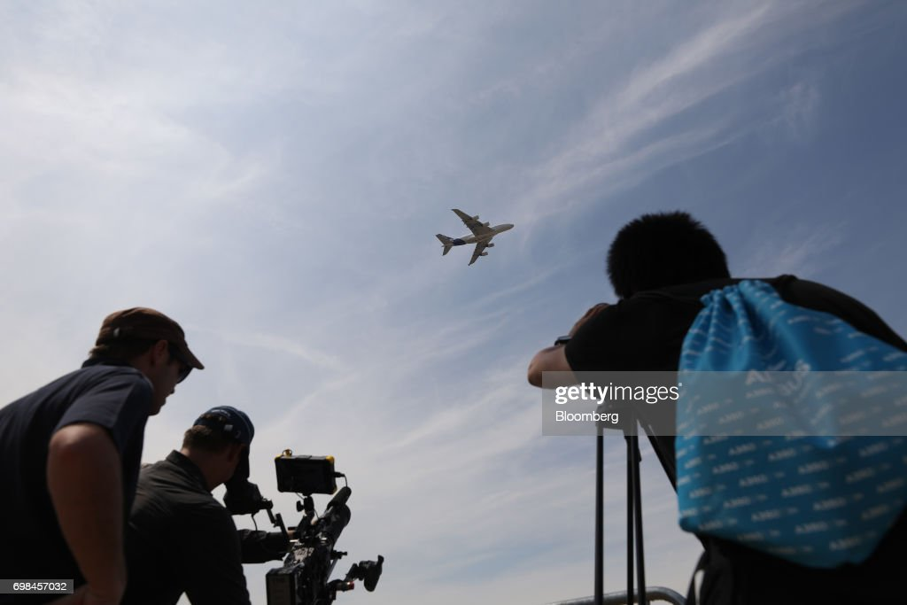 Attendees take photos and film as an Airbus SE A380 performs during a flying display at the 53rd International Paris Air Show at Le Bourget, in Paris, France, on Tuesday, June 20, 2017. The show is the world's largest aviation and space industry exhibition and runs from June 19-25. Photographer: Chris Ratcliffe/Bloomberg via Getty Images