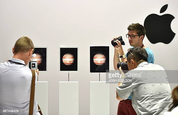 Attendees take photos and videos of new iPad Pro models on display during an Apple media event in San Francisco California on September 9 2015 Apple...