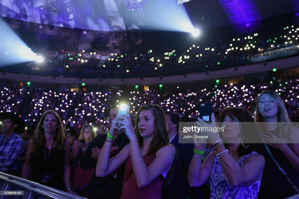 Attendees take photos with their cell phones during the 2016 iHeartCountry Festival at The Frank Erwin Center on April 30, 2016 in Austin, Texas.