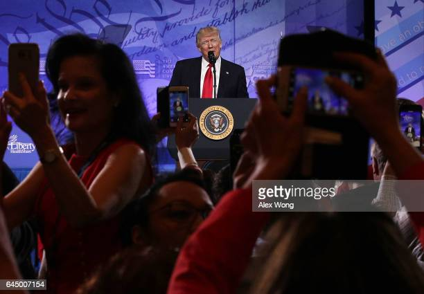 Attendees take pictures as US President Donald Trump addresses the Conservative Political Action Conference at the Gaylord National Resort and...