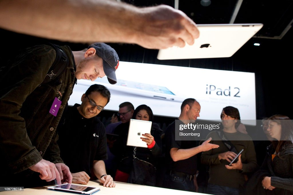 Attendees test out the new Apple Inc. iPad 2 at an event in San Francisco, California, U.S., on Wednesday, March 2, 2011. Chief Executive Office Steve Jobs, making his first public appearance since taking medical leave in January, unveiled a follow-up to a tablet computer released last April that has front and rear cameras, and a faster A5 chip. Photographer: David Paul Morris/Bloomberg via Getty Images