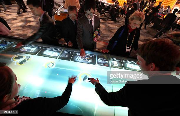 CES attendees touch an interactive touchscreen display in the Kodak booth during the 2010 International Consumer Electronics Show at the Las Vegas...
