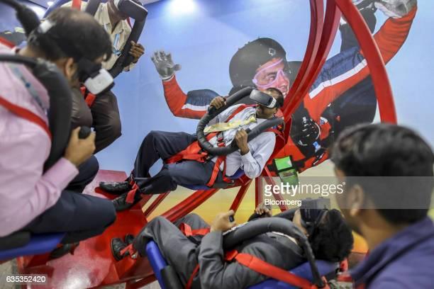 Attendees try a free fall simulator at the Hindustan Aeronautics Ltd booth during the Aero India air show at Air Force Station Yelahanka in Bengaluru...