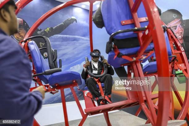 Attendees try a free fall simulator in the Hindustan Aeronautics Ltd booth during the Aero India air show at Air Force Station Yelahanka in Bengaluru...