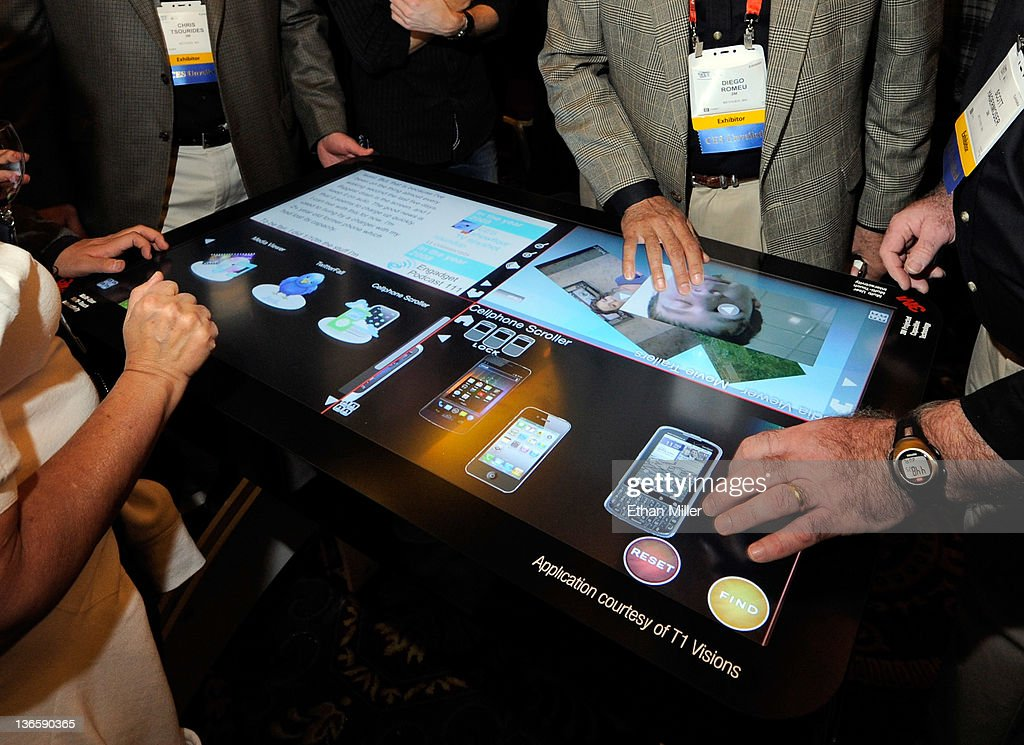 Attendees try a prototype 3M Touch Systems 46-inch, projected capacitive display during a press event at The Venetian for the 2012 International Consumer Electronics Show (CES) January 8, 2012 in Las Vegas, Nevada. The display utilizing technology from T1 Visions features a six-millisecond response to touch time, handles up to 20 finger touches at once and rejects accidental palm touches. CES, the world's largest annual consumer technology trade show, runs from January 10-13 and is expected to feature 2,700 exhibitors showing off their latest products and services to about 140,000 attendees.