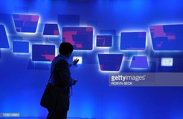 Attendees try an interactive display at the Microsoft booth at the 2010 International Consumer Electronics Show January 8 2010 in Las Vegas Nevada...