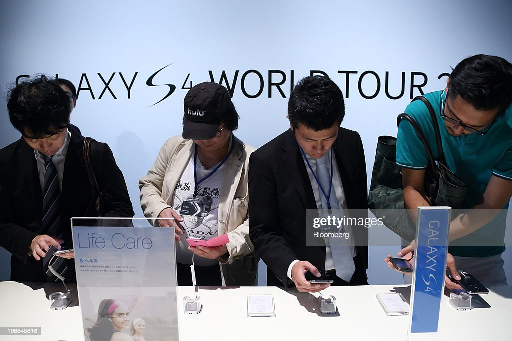 Attendees try Samsung Electronics Co. Galaxy S4 smartphones for NTT DoCoMo Inc. displayed during the Galaxy S4 World Tour 2013 Tokyo event in Tokyo, Japan, on Thursday, May 16, 2013. Samsung Electronics reported a record quarterly profit in April for the three months ended March 31. Photographer: Tomohiro Ohsumi/Bloomberg via Getty Images