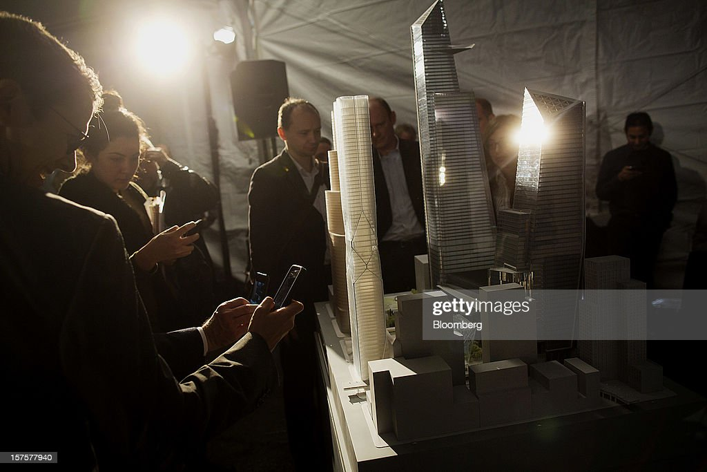 Attendees use cell phones to take photos of an architectural model of the Hudson Yards development during the groundbreaking ceremony in New York, U.S., on Tuesday, Dec. 4, 2012. Related Cos. has tentative deals in place for two more tenants to occupy the first tower of its Hudson Yards development, Chairman Stephen Ross said today as construction began at the 26-acre site on Manhattan's west side. Photographer: Victor J. Blue/Bloomberg via Getty Images