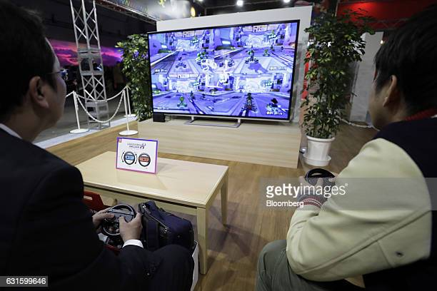 Attendees use JoyCon controllers with steering wheelshaped attachments while playing Mario Kart 8 Deluxe game on a Nintendo Co Switch games console...