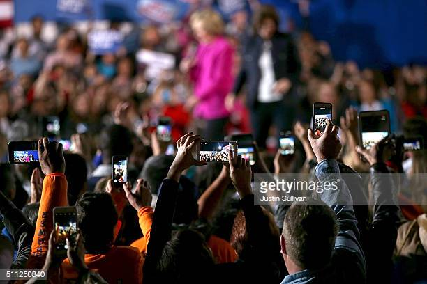 Attendees use mobile devices to photograph democratic presidential candidate former Secretary of State Hillary Clinton as she speaks during a 'Get...