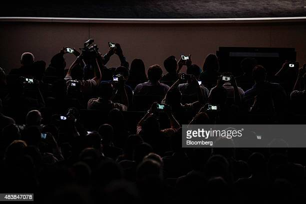Attendees use mobile devices to take photographs and videos during the Samsung Electronics Co Unpacked 2015 event in New York US on Thursday Aug 13...