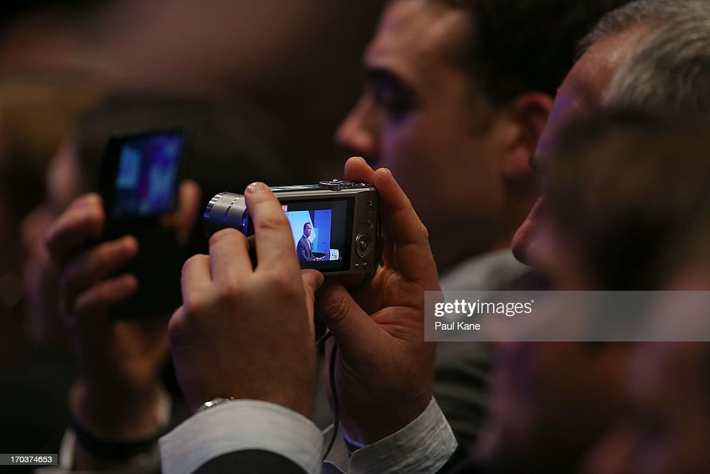 Attendees use their phones and cameras to film <a gi-track='captionPersonalityLinkClicked' href=/galleries/search?phrase=Arnold+Schwarzenegger&family=editorial&specificpeople=156406 ng-click='$event.stopPropagation()'>Arnold Schwarzenegger</a> speaking at the 2013 Financial Education Summit at the Perth Convention and Exhibition Centre on June 12, 2013 in Perth, Australia.