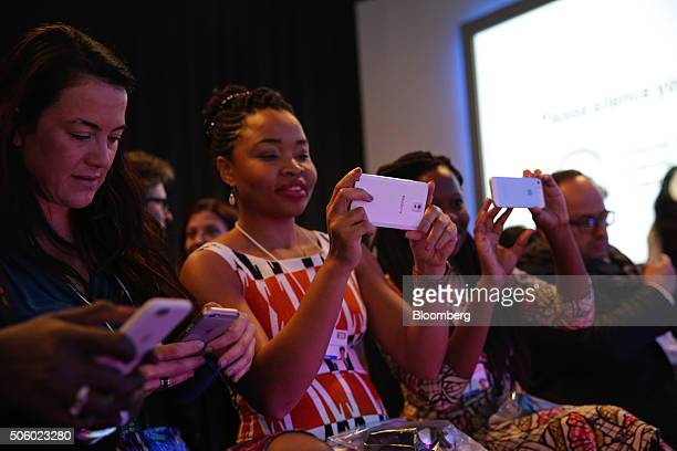 Attendees use their smartphone devices during a panel session at the World Economic Forum in Davos Switzerland on Thursday Jan 21 2016 World leaders...