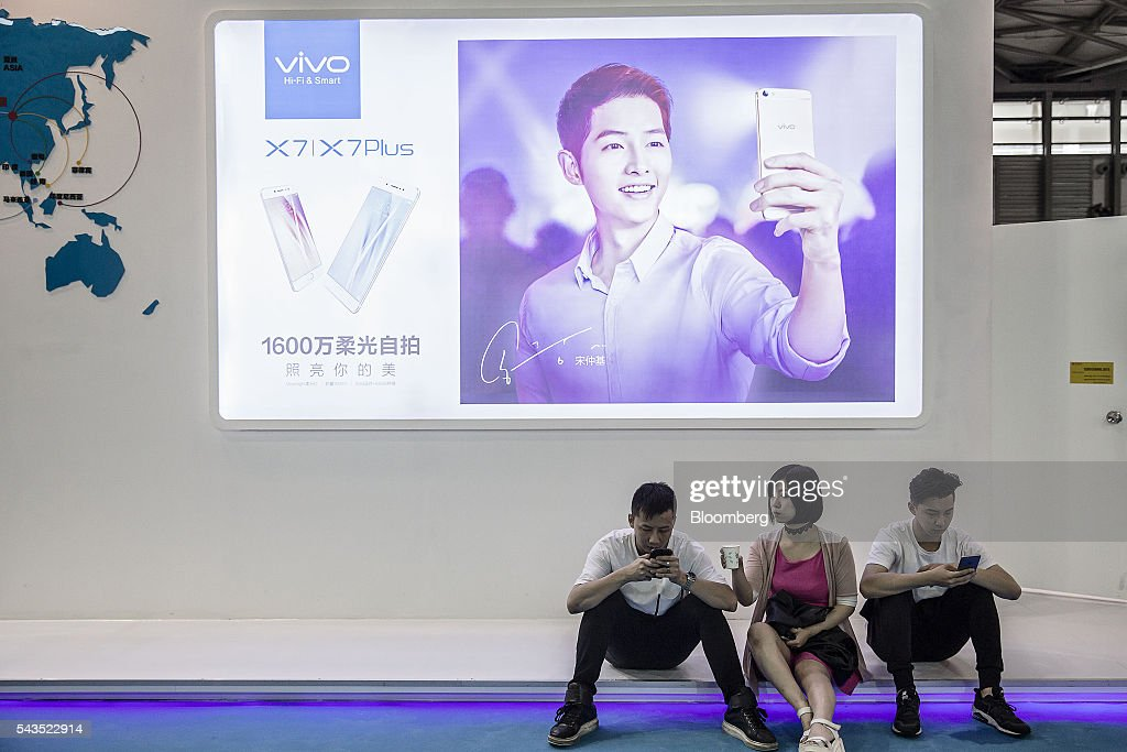 Attendees use their smartphones while seated in front of an advertisement for Vivo at the Mobile World Congress Shanghai in Shanghai, China, on Wednesday, June 29, 2016. The exhibition runs until July 1. Photographer: Qilai Shen/Bloomberg via Getty Images