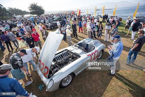 Attendees view a 1955 Daimler AG MercedesBenz 300 SLR vehicle during the 2015 Pebble Beach Concours d'Elegance in Pebble Beach California US on...