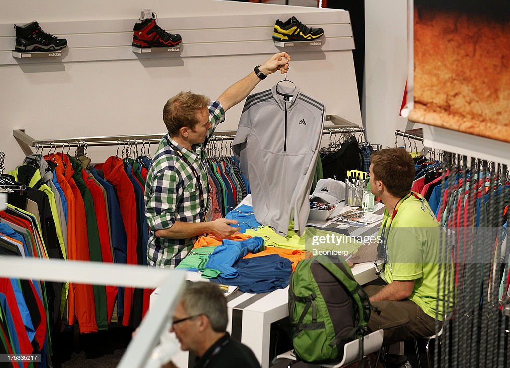 Attendees view Adidas AG clothes at the company's booth during the Outdoor Retailer Summer Market show in Salt Lake City, Utah, U.S., on Thursday, Aug. 1, 2013. Consumer spending in the U.S. rose in line with forecasts in June as Americans' incomes grew, a sign the biggest part of the economy is withstanding fiscal headwinds. Photographer: George Frey/Bloomberg via Getty Images