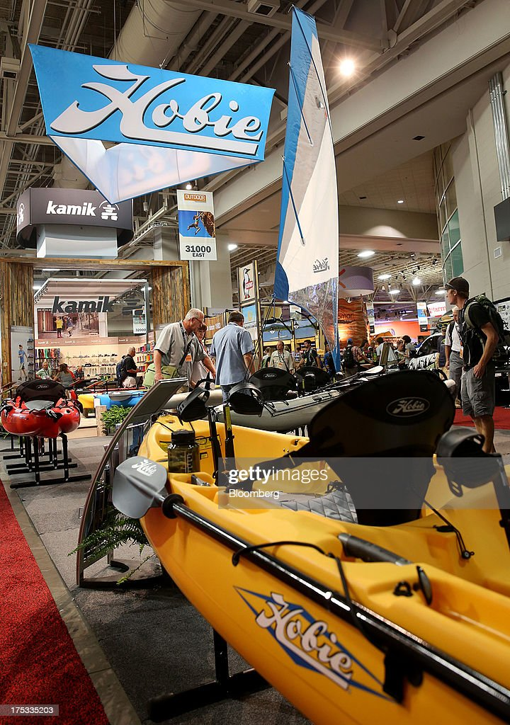 Attendees view Hobie water craft products at the company's booth during the Outdoor Retailer Summer Market show in Salt Lake City, Utah, U.S., on Thursday, Aug. 1, 2013. Consumer spending in the U.S. rose in line with forecasts in June as Americans' incomes grew, a sign the biggest part of the economy is withstanding fiscal headwinds. Photographer: George Frey/Bloomberg via Getty Images