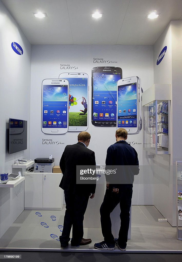 Attendees view Samsung Electronics Co. Galaxy S4 mobile phones displayed at the IFA consumer electronics show in Berlin, Germany, on Friday, Sept. 6, 2013. Global smartphone revenue will rise 22 percent in 2013, or nearly half the pace of an expected 41 percent gain in shipments, amid falling prices, according to UBS. Photographer: Krisztian Bocsi/Bloomberg via Getty Images