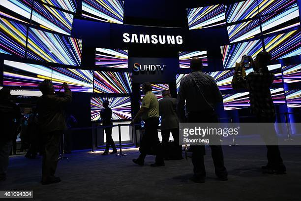 Attendees view Samsung Electronics Co SUHD 4K televisions during the 2015 Consumer Electronics Show in Las Vegas Nevada US on Tuesday Jan 6 2015 This...