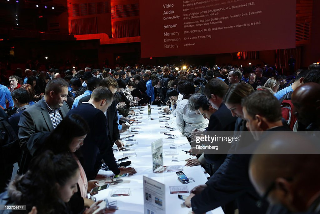 Attendees view the Samsung Electronics Co. Galaxy S4 smartphone during an event at Radio City Music Hall in New York, U.S., on Thursday, March 14, 2013. Samsung unveiled the Galaxy S4 with a bigger screen and software that tracks eye movements as the world's biggest smartphone seller takes its battle with Apple Inc. to the iPhone maker's home market. Photographer: Victor J. Blue/Bloomberg via Getty Images