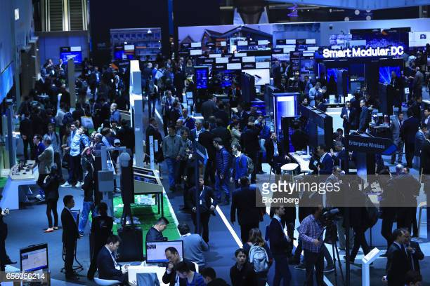 Attendees visit corporate pavilions in an exhibition hall at the CeBIT 2017 tech fair in Hannover Germany on Tuesday March 21 2017 Leading edge...
