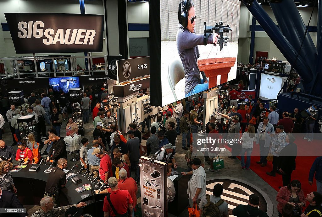Attendees visit the Sig Sauer booth during the 2013 NRA Annual Meeting and Exhibits at the George R. Brown Convention Center on May 4, 2013 in Houston, Texas. More than 70,000 peope are expected to attend the NRA's 3-day annual meeting that features nearly 550 exhibitors, gun trade show and a political rally. The Show runs from May 3-5.