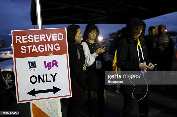 Attendees wait for rides in the Uber Technologies Inc and Lyft Inc reserved staging area during the 2016 Consumer Electronics Show in Las Vegas...