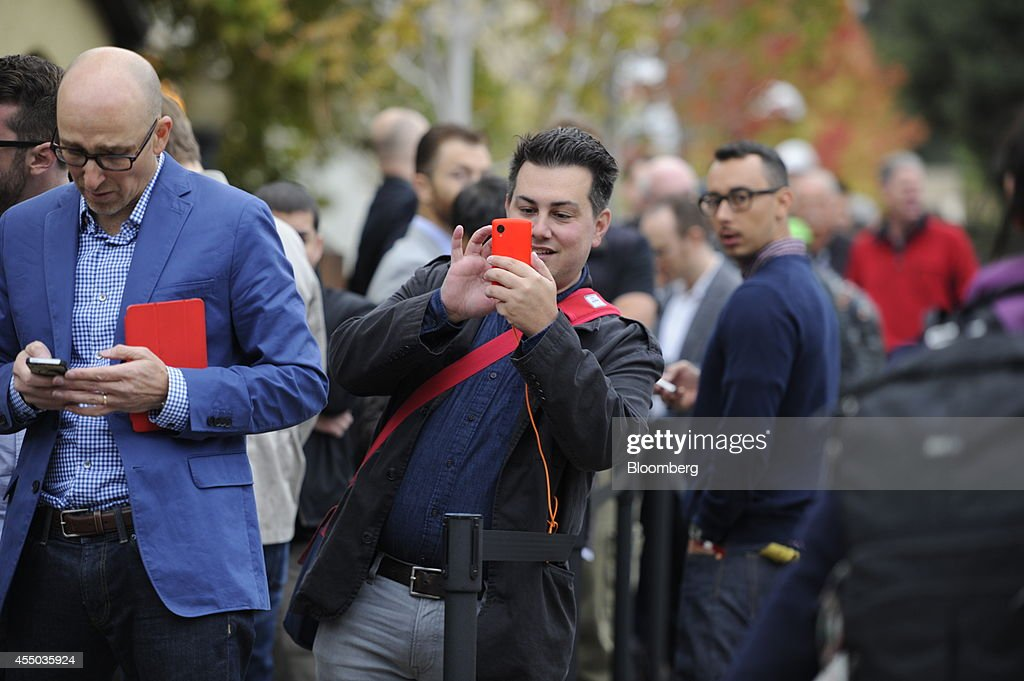 Attendees wait in line ahead of a product announcement at Flint Center in Cupertino California US on Tuesday Sept 9 2014 Apple Inc is expected to...