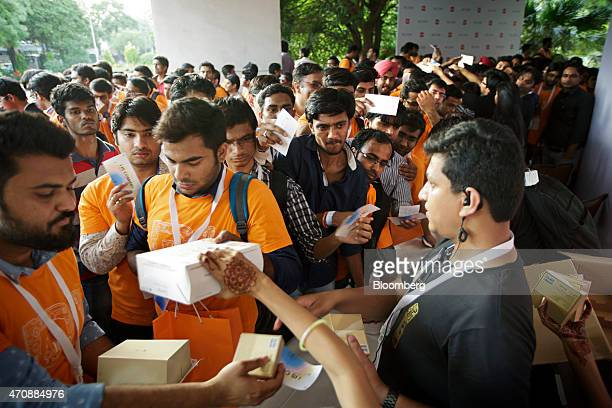 Attendees wait in line to receive free Xiaomi Corp Mi Bands following a launch event in New Delhi India on Thursday April 23 2015 Xiaomi unveiled the...