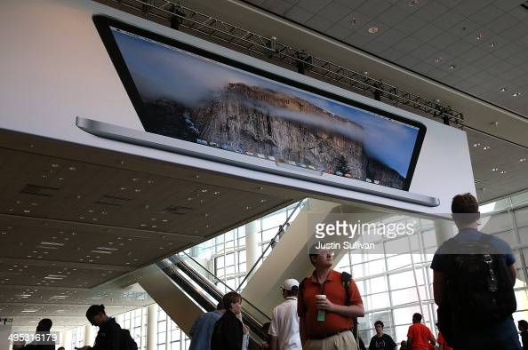 Attendees walk by a poster for the new Apple OSX Yosemite operating system at the Apple Worldwide Developers Conference at the Moscone West center on...