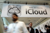 Attendees walk by a sign for the new iCloud during the 2011 Apple World Wide Developers Conference at the Moscone Center on June 6 2011 in San...