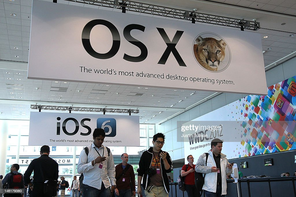 WWDC attendees walk by posters for the new OSX Mountain Lion operating system and iOS 6 operating system for iPhone following the keynote address at the Apple 2012 World Wide Developers Conference (WWDC) at Moscone West on June 11, 2012 in San Francisco, California. Apple unveiled a slew of new hardware and software updates at the company's annual developer conference which runs through June 15.