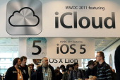 Attendees walk by signs for the new iCloud and iOS5 during the 2011 Apple World Wide Developers Conference on June 6 2011 at the Moscone Center on...
