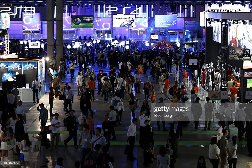 Attendees walk near a booth for Sony Computer Entertainment Inc. PlayStation 4 (PS4) at the Tokyo Game Show 2013 in Chiba, Japan, on Thursday, Sept. 19, 2013. Sony Corp. expects sales of its new PlayStation 4 console to reach 5 million units this financial year, with at least 20 games to be available as it competes with a new machine from Microsoft Corp. Photographer: Kiyoshi Ota/Bloomberg via Getty Images