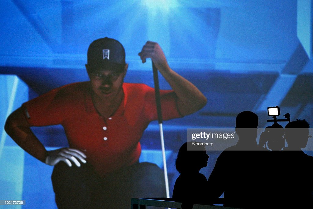 Attendees walk near a video screen for Electronic Arts Inc.'s Tiger Woods PGA Tour 11 game during the Electronic Entertainment Expo (E3) in Los Angeles, California, U.S., on Wednesday, June 16, 2010. Nintendo Co., Sony Corp., and Microsoft Corp. showed off 3-D and motion sensing capabilities for video games as the companies look to additional features to revive shrinking industry sales. Photographer: Jonathan Alcorn/Bloomberg via Getty Images