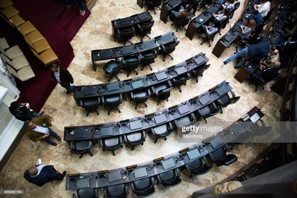 Attendees walk near empty pro-government deputies' chairs during a special session of the National Assembly of Caracas, Venezuela, on Saturday, Aug. 19, 2017. Venezuela's new legislative super body took over the functions of the country's only remaining opposition-run institution -- the National Assembly -- by approving a decree that empowers it to pass laws on a range of issues. Photographer: Wil Riera/Bloomberg via Getty Images