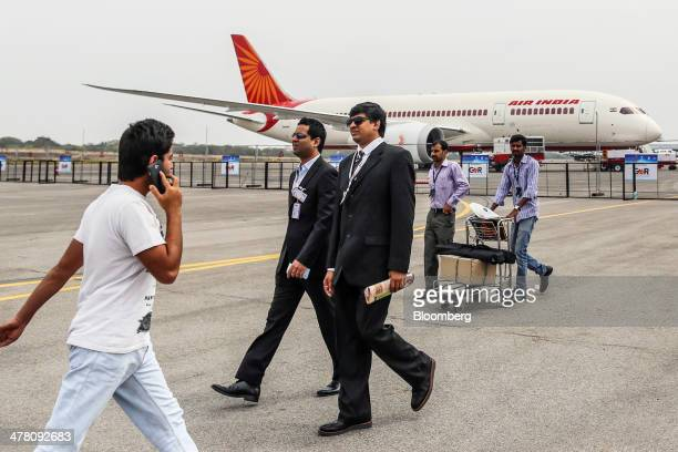 Attendees walk past a Boeing Co 787 Dreamliner aircraft operated by Air India Ltd on display during the India Aviation 2014 air show held at Begumpet...