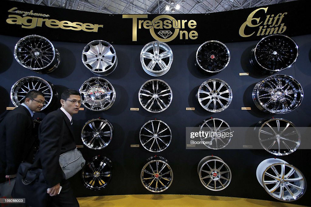 Attendees walk past a display of Treasure One Company Co. wheel caps at the Tokyo Auto Salon 2013 at Makuhari Messe in Chiba, Japan, on Friday, Jan. 11, 2013. The Tokyo Auto Salon runs until Jan. 13. Photographer: Kiyoshi Ota/Bloomberg via Getty Images