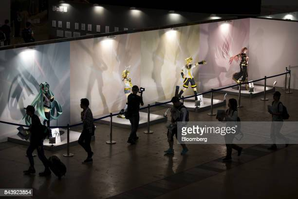 Attendees walk past a figure of Hatsune Miku a virtual pop star and the voice behind Crypton Future Media Inc's vocal synthesizer softwareleft and...
