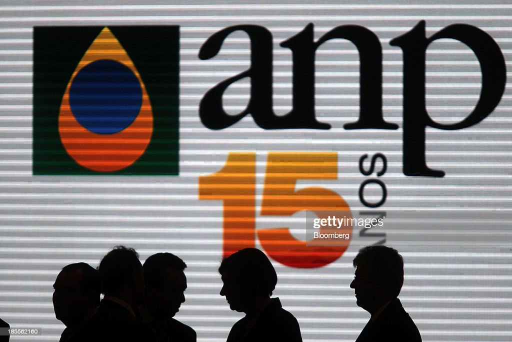 Attendees walk past a screen displaying the logo of Brazil's National Oil Agency (ANP) during the Libra oilfield auction in Rio de Janeiro, Brazil, on Monday, Oct. 21, 2013. A group led by Petroleo Brasileiro SA won a license to develop Brazils biggest oil discovery under more favorable terms than analysts estimated. Shares in Petrobras, as the state-run producer is known, surged. Photographer: Dado Galdieri/Bloomberg via Getty Images