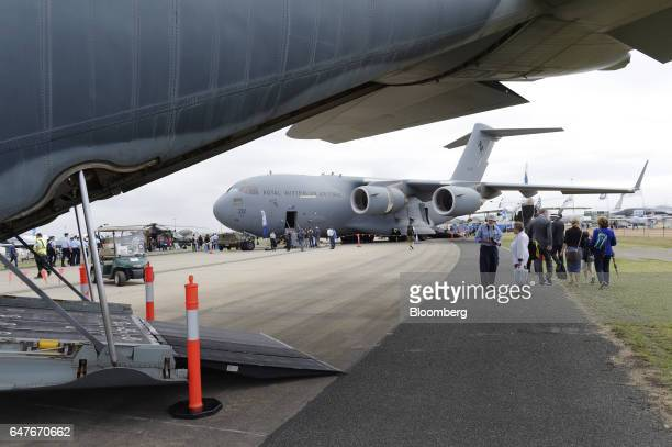 Attendees walk past an Australian Defence Force C130J Super Hercules turboprop military transport aircraft manufactured by Lockheed Martin Corp on...