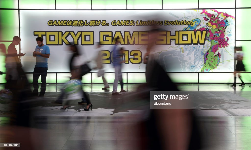 Attendees walk past signage displayed at the entrance to the Tokyo Game Show 2013 in Chiba, Japan, on Thursday, Sept. 19, 2013. The Tokyo Game Show runs till Sept. 22. Photographer: Tomohiro Ohsumi/Bloomberg via Getty Images