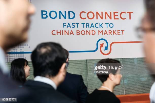 Attendees walk past signage for the ChinaHong Kong Bond Connect at the Hong Kong Stock Exchange in Hong Kong China on Monday July 3 2017 The first...