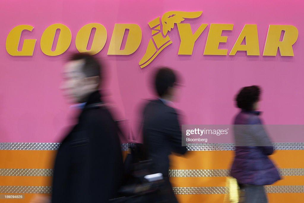 Attendees walk past the Goodyear Tire & Rubber Co. logo at the Tokyo Auto Salon 2013 at Makuhari Messe in Chiba, Japan, on Friday, Jan. 11, 2013. The Tokyo Auto Salon runs until Jan. 13. Photographer: Kiyoshi Ota/Bloomberg via Getty Images